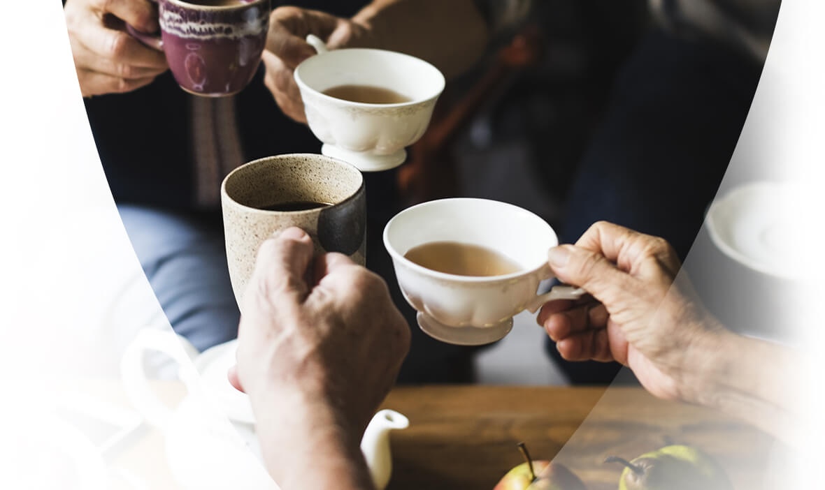 Group of people cheers with cups of tea.